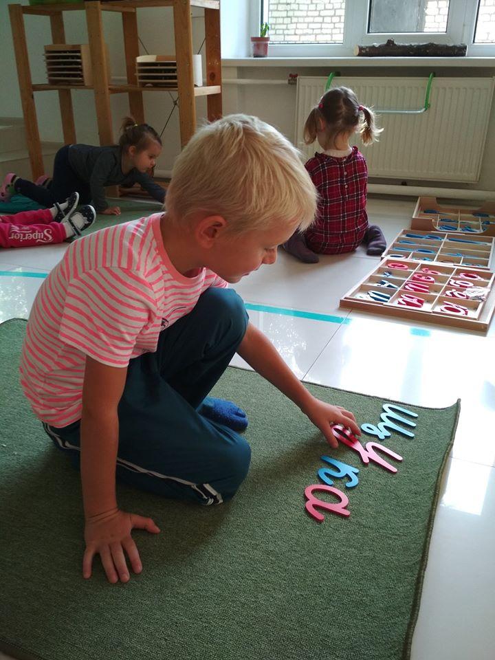 Мальчик выкладыват слова из подвижного алфавита